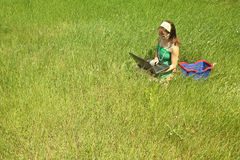 Girl in grass with laptop Stock Images