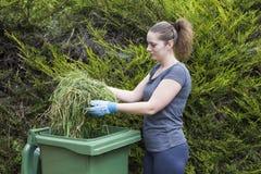Girl with grass near green bin Stock Photos