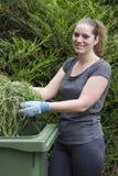 Girl with grass near green bin Stock Photo