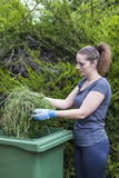 Girl with grass near green bin Stock Images