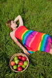 Girl on the grass next to a basket of apples Stock Images