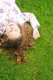 Girl on grass in park. Over head view of a young girl laying down on green grass with her eyes shut Royalty Free Stock Image