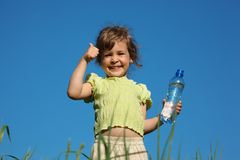 Girl in grass with plastic bottle with water Royalty Free Stock Image