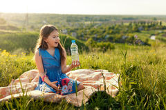 Girl in grass with plastic water bottle Royalty Free Stock Image