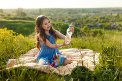 Girl in grass with plastic water bottle Royalty Free Stock Images