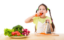 Girl with grater eating the carrots Stock Photos