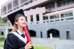 Girl gratuate think of future. With diploma hoding in hand stock images