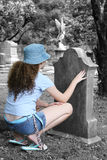 Girl In Graveyard 1. A young girl looking at a tombstone in a graveyard royalty free stock images