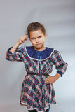 Girl on gray background a dress deep in thought Stock Images