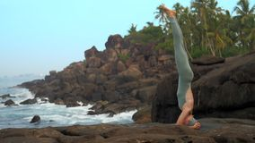 Girl in gray bodysuit shows sirsasana by ocean slow motion. Graceful girl in gray bodysuit shows sirsasana pose standing on large rock at calm ocean in morning stock video footage