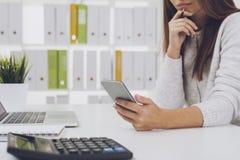 Girl in gray cardigan looking at smart phone screen Stock Photo
