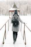 Girl in gray coat on a bridge in winter. Girl in a gray coat and a gray hat with a black backpack on a bridge in winter, rear view Stock Photos