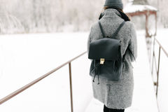 Girl in gray coat on a bridge in winter. Girl in a gray coat and a gray hat with a black backpack on a bridge in winter, rear view Royalty Free Stock Photos