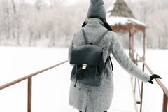 Girl in gray coat on a bridge in winter. Girl in a gray coat and a gray hat with a black backpack on a bridge in winter, rear view Royalty Free Stock Images