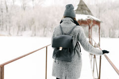 Girl in gray coat on a bridge in winter. Girl in a gray coat and a gray hat with a black backpack on a bridge in winter, rear view Stock Images