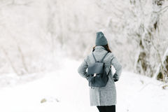 Girl in gray coat on a bridge in winter. Girl in a gray coat and a gray hat with a black backpack on a bridge in winter, rear view Royalty Free Stock Photography