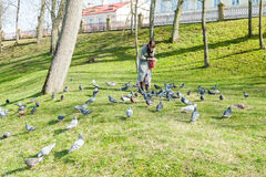A girl in a gray coat feeds a flock of pigeons Royalty Free Stock Photography
