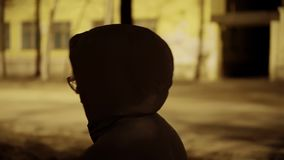 A girl in a gray coat with a hood on her head is op night city. The atmosphere of a night walk. The view from over her shoulder. Close-up in motion stock footage