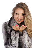 Girl in a gray coat with open hands palm. Attractive smiling woman in a gray coat with open hands palm for product Royalty Free Stock Images