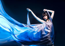 Girl in a gray dress flying with blue backlight Stock Image