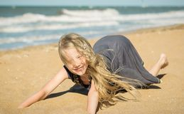 The girl in the gray dress on the sand by the ocean. Royalty Free Stock Photo