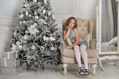 Girl in a gray dress sitting in a chair at the Christmas tree Stock Photos