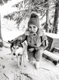 Girl in a gray hat and blue jacket with a husky dog in winter. husky kennel.