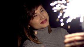 A girl in a gray jumper, bangs and a piercing in the nose holds a sparkler in front of her face. A girl in a gray jumper, bangs and a piercing in the nose holds stock footage