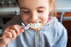 A girl in a gray patch of a sweater holds an Easter egg on her wand in her hand. Little girl eating easter bunny ginger biscuit cl Stock Photography