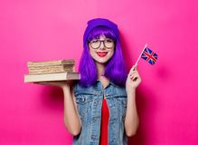 Girl with Great Britain flag and books. Portrait of young style hipster girl with purple hair and Great Britain flag in hand and books on pink background Royalty Free Stock Photography