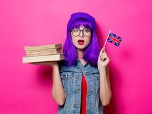 Girl with Great Britain flag and books. Portrait of young style hipster girl with purple hair and Great Britain flag in hand and books on pink background Stock Images