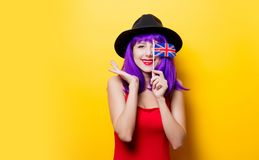 Girl with Great Britain flag in hand. Portrait of young style hipster girl with purple hairstyle and Great Britain flag in hand on yellow background Royalty Free Stock Photography