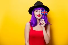 Girl with Great Britain flag in hand. Portrait of young style hipster girl with purple hairstyle and Great Britain flag in hand on yellow background Stock Images