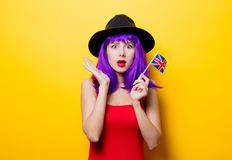 Girl with Great Britain flag in hand. Portrait of young style hipster girl with purple hairstyle and Great Britain flag in hand on yellow background Royalty Free Stock Photos