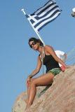 Girl and the greek flag. / Lighthouse Santorini Greece / Woman Natural Pose stock photo