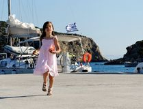 Girl in Greek harbor. Little girl running in Greek harbor with background of cliffs, yacht and sea royalty free stock photo