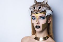 Athena make up. Girl in the Greek style. With big massive golden necklace on her neck, hat helmet stuffed lynx on her head. Creative make-up new conceptual idea Royalty Free Stock Images