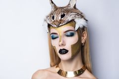 Athena make up. Girl in the Greek style. With big massive golden necklace on her neck, hat helmet stuffed lynx on her head. Creative make-up new conceptual idea Royalty Free Stock Photo