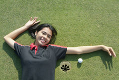 Girl on green. Young, female golf player smiling and embracing the hole at a colf course Royalty Free Stock Images