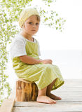 Girl in green. Little girl sitting at beam Royalty Free Stock Images