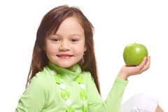 A girl with a green apple. A smiling girl in a green dress holding a green apple in her hand Stock Photos