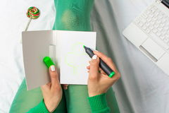 Girl in green drawing a clover Stock Photography
