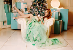 Girl in green dress with Christmas tree Stock Photos