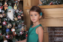 Girl in a green dress near a Christmas tree Stock Photos