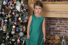 Girl in a green dress near a Christmas tree Stock Photography