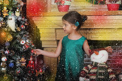 Girl in a green dress near a Christmas tree Stock Images