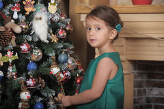 Girl in a green dress near a Christmas tree Royalty Free Stock Photo
