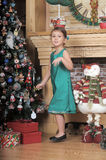 Girl in a green dress near a Christmas tree Stock Image