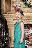 Girl in a green dress near a Christmas tree Royalty Free Stock Image