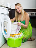 Girl in green dress using washing machine Royalty Free Stock Images